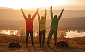 Happy hikers with arms raised enjoying sunset in nature
