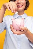 Crop woman saving money in piggy bank