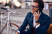 Positive businessman talking on smartphone on street