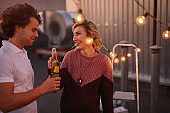 Cheerful couple drinking beer and chatting during party