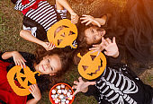 Happy kids with pumpkin masks relaxing on grass