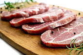 Sliced raw pork meat with fresh rosemary and pepper on cutting board