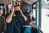 Young man wearing protective mask while riding a bus