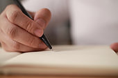 Close up of hand holding pen and writing on empty book paper, selective focus