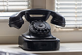 An old black retro telephone with a handset is on the windowsill