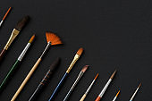 Paintbrushes for watercolor painting. top view, flat lay. Different shape and size paint brushes on black paper sheet. Set of brushes for watercolor, acrylic or oil painting.
