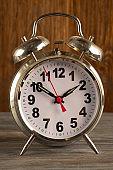 Big old vintage alarm clock with bells, dark wooden background