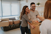 Portrait of attractive young couple moving in to new home. Young man is holding cardboard box while his wife taking keys of their new home from real estate agent.