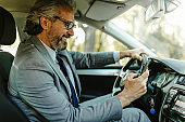 A smiling mature businessman driving a expensive car holds a mobile phone in his hand.