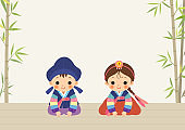 Children in Hanbok on the background of bamboo and hardwood floor.Korean New Year's Day.New Year's greetings.