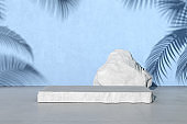 3D rendering of white stone podium for product presentation on blue concrete wall with palm leaf shadow.