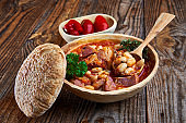 Smoked pork and beans stew on a rustic table