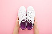 Young adult woman hands holding white female sport shoes for walking, running or fitness on light pink table background. Pastel color. Closeup. Point of view shot. Top down view.