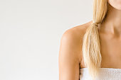 Young adult woman with blond hair in white towel isolated on light gray background. Closeup. Front view. Empty place for text. Female body care concept.