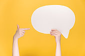 Close up of unrecognizable young female holding and pointing at blank white paper speech bubble, isolated on yellow background with copy space for advertisement. Body language concept