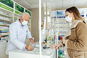 Shopping prescription drugs and pharmacist's advice, prescription drugs. A side view of a pharmacist standing behind a counter selling medicine to an adult girl wearing a protective mask