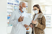 Reading prescription drugs, talking between a pharmacist and a client. An adult female customer seeks advice from an experienced pharmacist on the recommended therapy Protective masks and corona virus