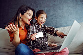 Smiling mother and daughter sitting on sofa and using laptop for online shopping. Daughter holding credit card and pointing at toy on laptop she want to buy.