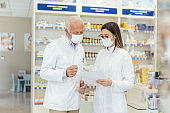 Colleague advice. Documentation and paper work in pharmacies during corona virus. A senior pharmacist explains the documentation in the pharmacy to a young pharmacist They wear uniforms and face masks
