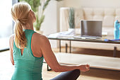 Back view of mature blonde woman sitting in lotus position on the floor and watching online training using laptop at home in the daytime