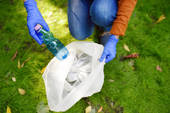 Volunteer picking up the plastic garbage and putting it in biodegradable trash-bag on outdoors. Ecology, recycling and protection of nature. Environmental protection.