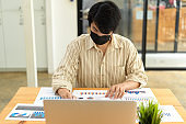 Portrait of businessman with face mask working with paperwork and laptop
