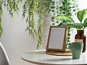 Coffee table with mock up frame, mug and houseplants decorated in Biophilia leisure corner