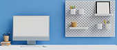 Computer with mock-up screen on white table with stationery and decoration on shelf on blue wall, 3D rendering