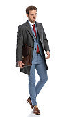 confident elegant man holding suitcase, walking and looking to side