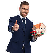 confident real estate agent showing building model