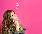 Idea concept - Young thoughtful caucasian girl eight years old looking up with finger on face contemplation in front of pink background - copy space