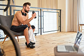 Athletic young man with bottle of water resting after home workout