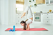 Stretch the limits. Full length shot of beautiful hispanic teenage girl wearing sportswear practicing yoga, doing exercises on a mat at home