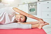 Fit and healthy. Close up of happy hispanic teenage girl wearing sportswear smiling at camera while doing splits, stretching her body on a mat at home