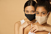 Two attractive young women, female friends wearing protective facial masks while posing together isolated over beige background