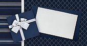 Gift card and gift box with ribbon and bow isolated on elegant blue fabrics background, top view and copy space template, useful for father's day greeting