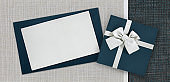 Gift card and gift box with ribbon and bow isolated on elegant blue and grey fabrics background, top view and copy space template, useful for father's day greeting