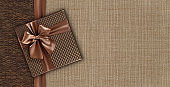 Gift card with gift box with ribbon and bow isolated on elegant brown fabrics background, top view and copy space template, layout useful for best wishes and shopping concept