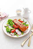 Salmon fish fillet grilled and vegetable salad with radish, tomato, green pepper, broccoli and asparagus.