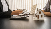 House model with agent and customer discussing for contract to buy, get insurance or loan real estate or property.