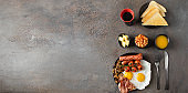 Top view of Full English breakfast  on concrete background.  Fried eggs, sausages, bacon, beans, mushrooms, toasts, butter, coffee, juice