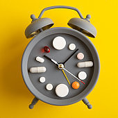 Creative healthcare and medicine concept - clock with drugs and pills.Right time for using medicines. Cold and flu season. Period of diseases