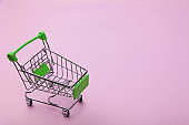 Empty supermarket shopping grocery cart on colored background