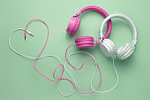 Cute image of two headphones whith cables in heart shape over cyan background. Music concept.