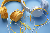 Close-up photo of two stylish headphones over blue background. Music concept.