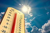 low angle view Thermometer on blue sky with sun shining