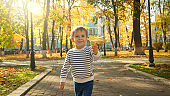Portrait of cute little boy holding yellow autumn lef and running towards the camera at park