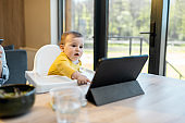 Baby and parents busy in a digital gadgets during a lunch at home