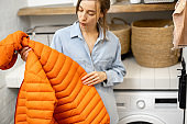 Young housewife looks on a down jacket before washing