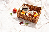 Morning breakfast in a wicker basket on a white bed sheet. Cup of coffee, fruit and a delicious bun